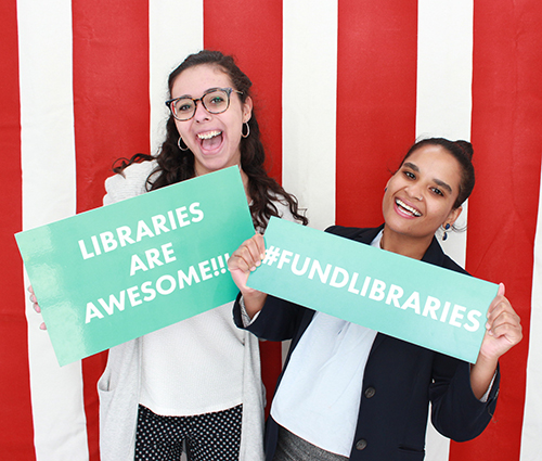 "Two women holding signs that say ""Libraries are awesome!!!"" and ""#FundLibraries"""