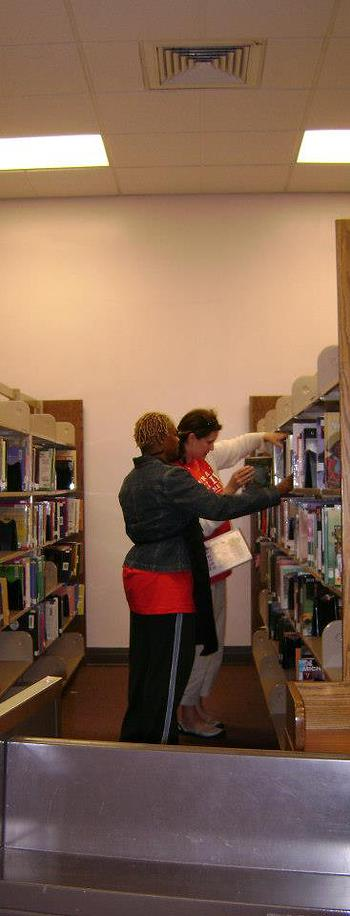 Two women standing at bookshelves