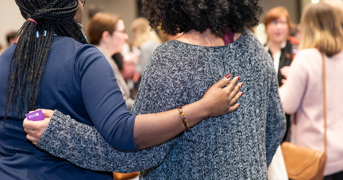 Image of two people putting their arms around each other's backs