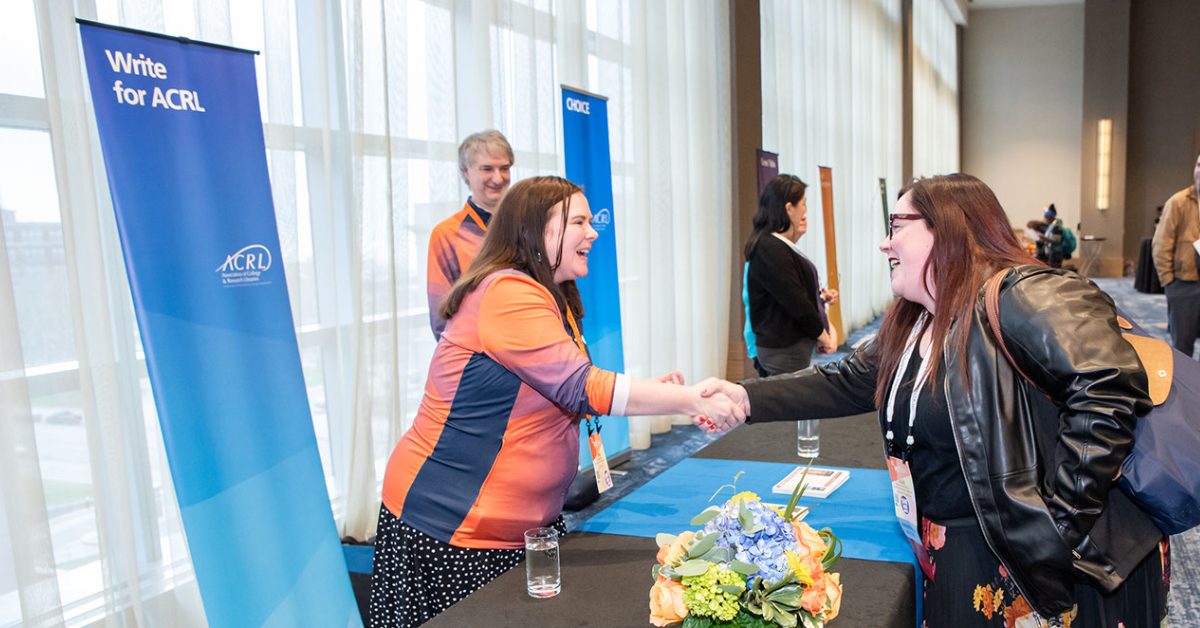 "Photo of a conference attendee shaking hands with an ACRL staff member with a sign behind them that says ""Write for ACRL"""