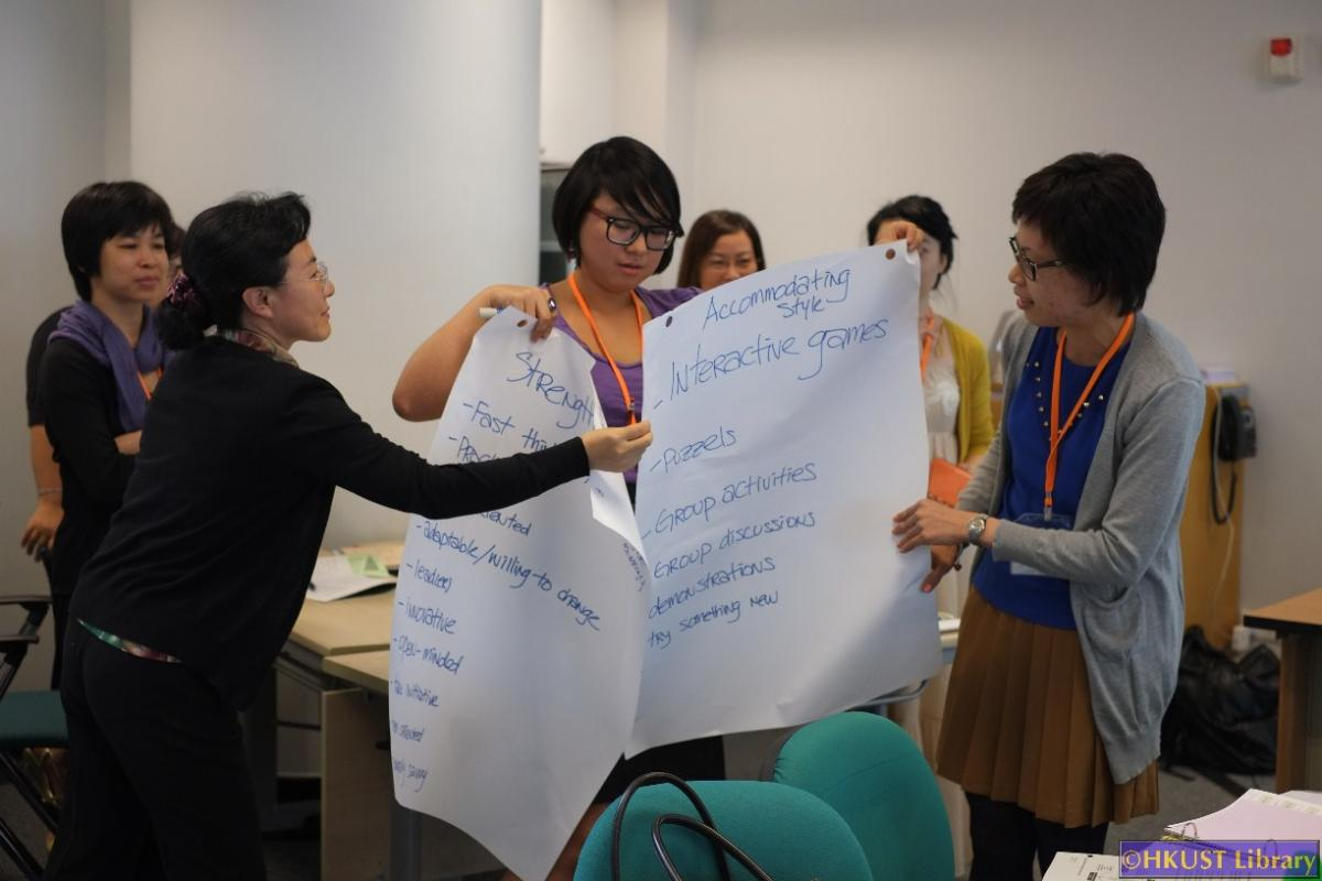 Immersion Program attendees organizing flipcharts.