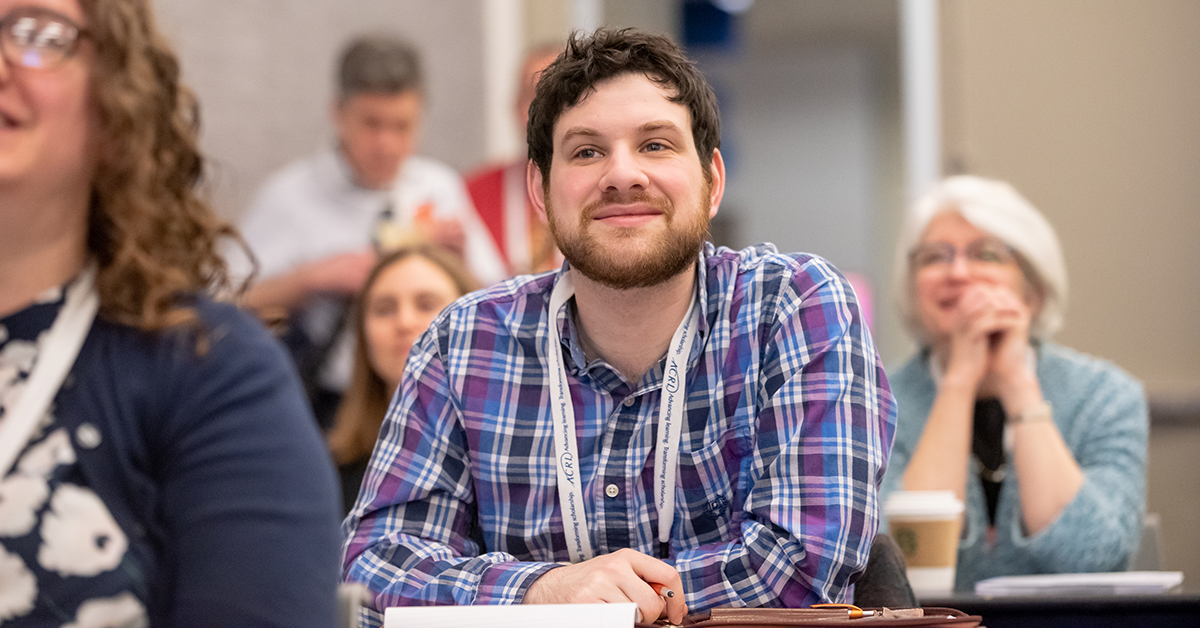 Photo of man at a table smiling