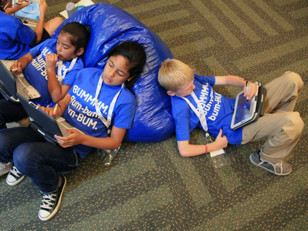 Kids relaxing and reading on beanbag chair and floor.