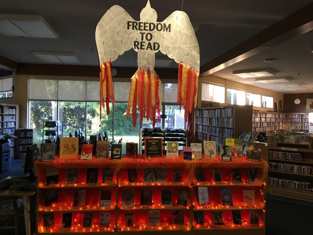 An outline of a bird wallpapered with book pages hangs above a shelf of books. The shelves have orange tealights strung across them.