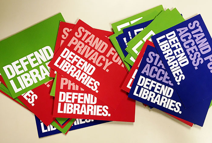 Defend libraries postcards scattered on a desk