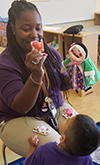 Eboni Henri entertaining a young student with puppets