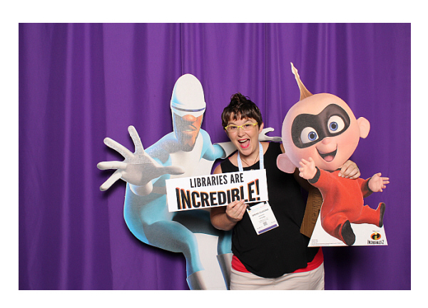 Photobooth: Librarian with Frozone and Jack Jack standees holding a sign that reads: Libraries are Incredible