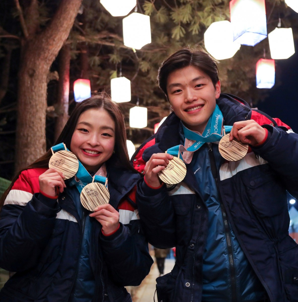 Maia and Alex Shibutani holding their Olympic Medals.