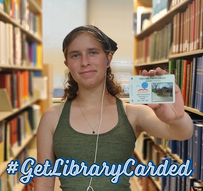 Young woman standing in a library holding a library card.