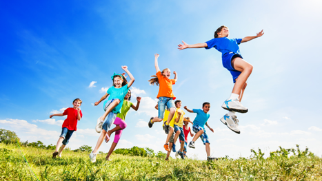 Photo of happy children running and jumping in open field