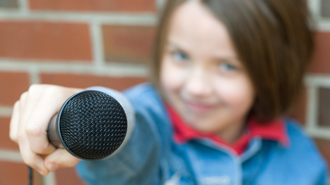 Photo of a young girl pointing a microphone at the camera