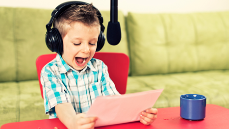 Photo of young boy at desk with headphones on, reading into a microphone