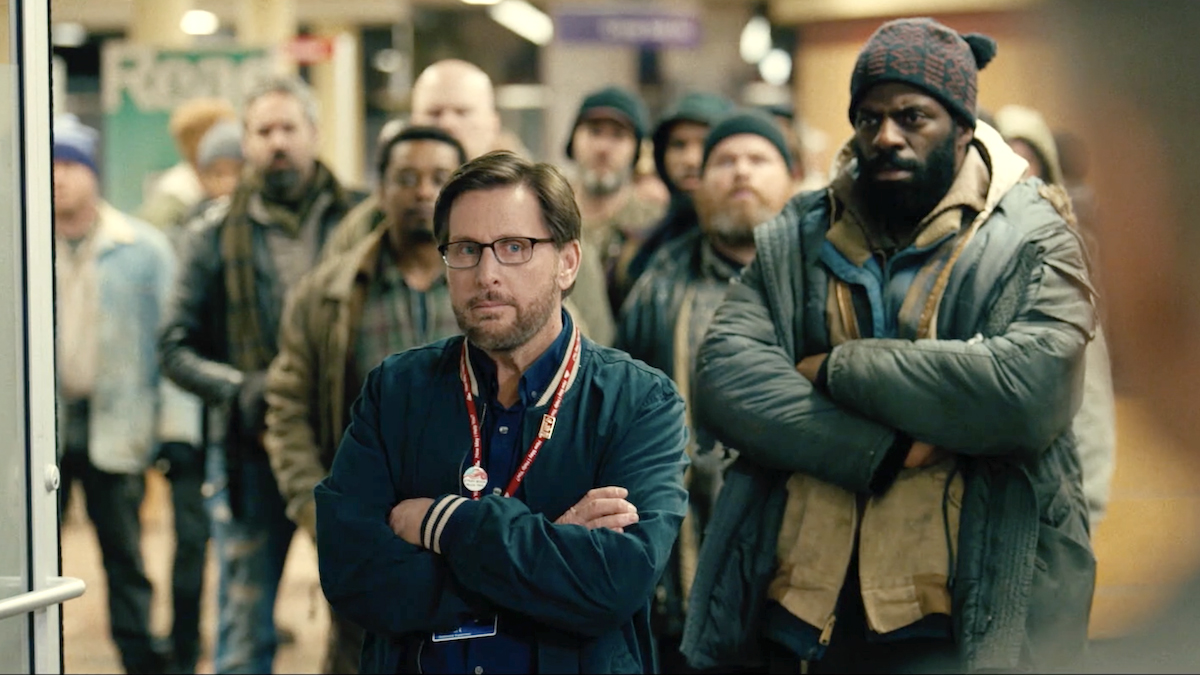"Screenshot from ""The Public"" movie, Emilio Estevez with homeless library patrons"