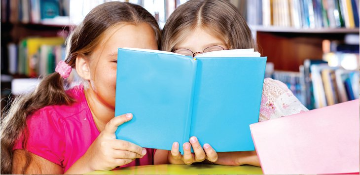 Two girls sharing a book in a school library