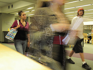 Students rushing past a reserve desk at an academic library.