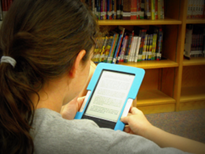 Teen girl at library with e-reader