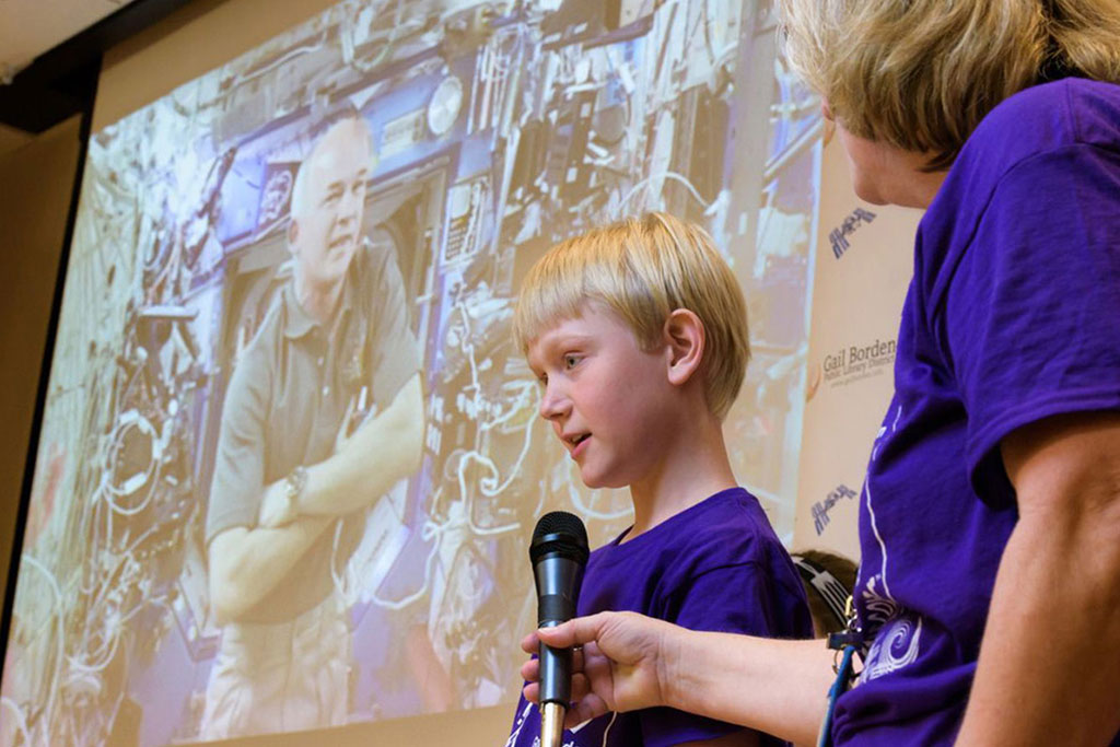 Fifth-grader Evan Sass asks NASA astronaut Jeff Williams a question via video chat at Gail Borden Public Library. The Elgin, Illinois, library was one of eight nationwide selected for the traveling exhibit, Discover Space: A Cosmic Journey.