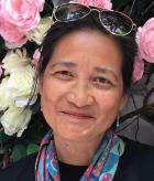 Photo of Miriam Tuliao in front of flowers