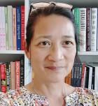 Miriam Tuliao in front of bookshelf