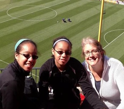 Cindy Fesemyer takes in a soccer game with daughters Siena and Clara