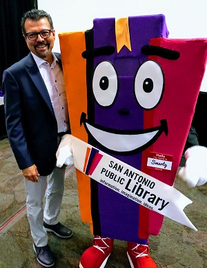 "Ramiro Salazar poses with ""Smarty,"" the San Antonio Public Library mascot"