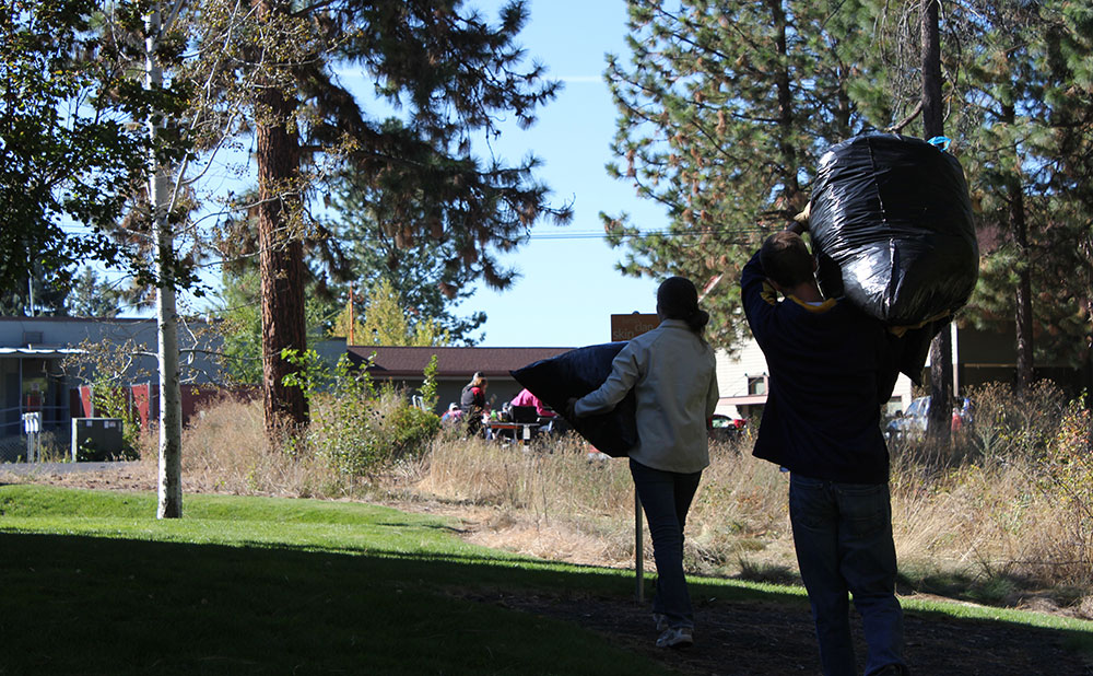 Community members help clean up a trash-strewn park.