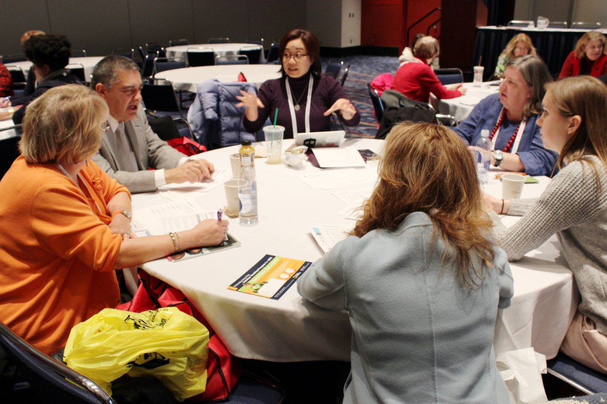 A group of people sitting around a table talking at an ALA conference session