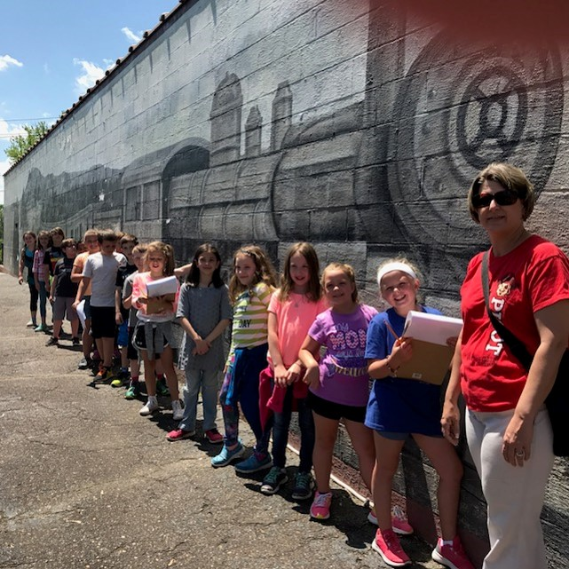 Students in front of train mural