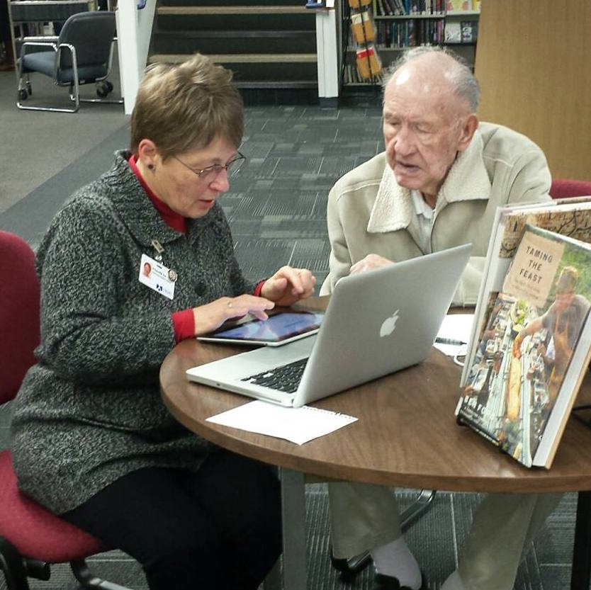 A Spokane County Library District employee helping a patron with a tablet computer