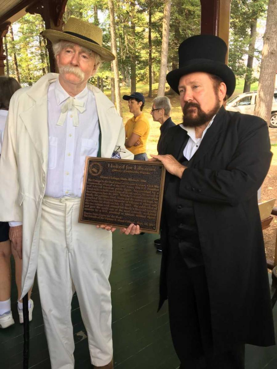 Two gentlemen in 1800's style attire hold an honorary plaque on the porch of Grant Cottage.