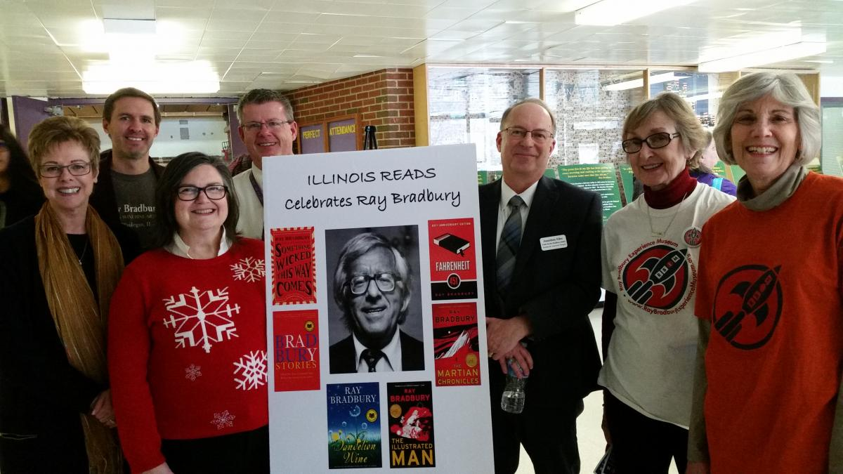 "Attendees of the Illinois Reads Festival hold up a presentation board titled, ""ILLINOIS READS Celebrates Ray Bradbury."""