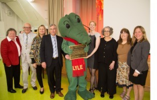 "From left: Virginia Stanley, board member, United for Libraries; Rocco Staino, director, Empire State Center for the Book; Betsy Groban, SVP and publisher, Houghton Mifflin Harcourt Books for Young Readers; Gary Gentel, president, HMH Trade and Consumer Publishing; Lyle the Crocodile; Mary Wilcox, VP and editorial director, HMH Books for Young Readers; Paulis Waber, daughter of Bernard Waber and illustrator of ""Lyle Walks the Dogs""; librarian Margaret Tice, and Samantha Kaplan, principal, Yorkville Community School. Photo credit: Mason Cash."